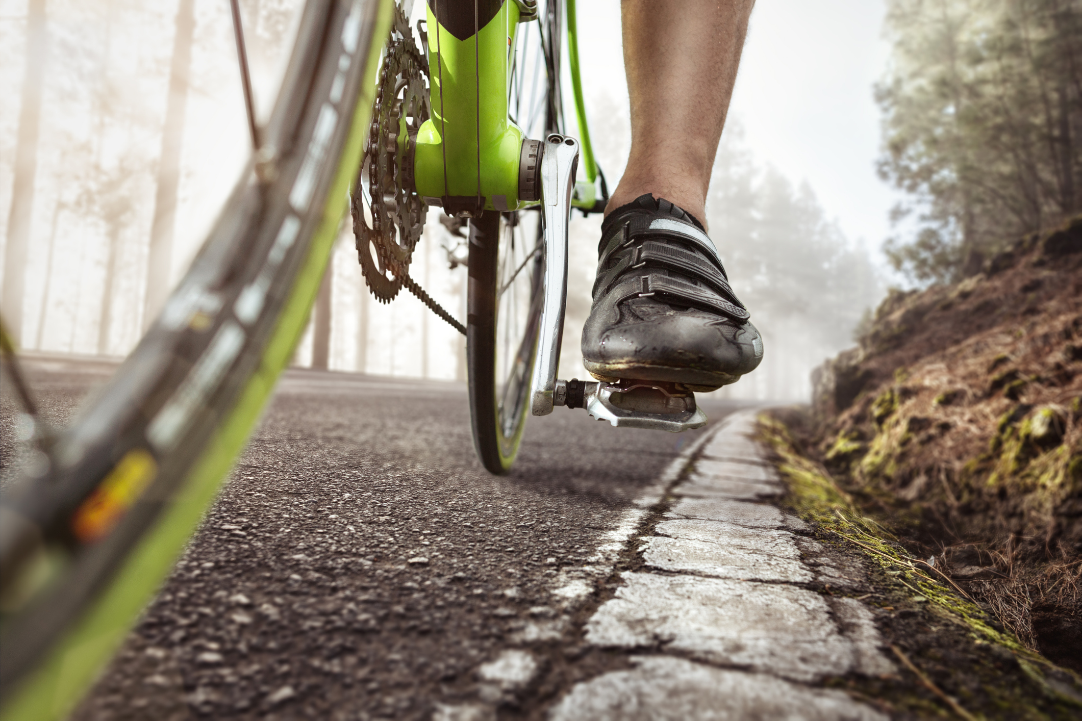 Pedal and shoe of a racing bicycle. Shot from a low angle with cracked road markings in the foreground.